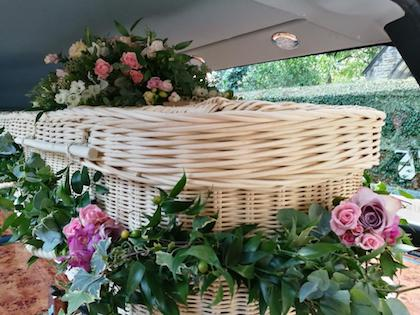 willow coffin decorated with pink posies